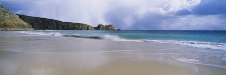 Waves breaking on the beach Logan Rock Porthcurno