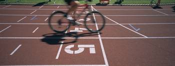 Low section view of a man cycling on sports track