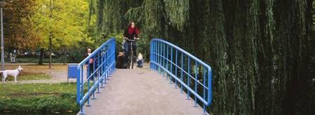 Woman riding a bicycle on a footbridge