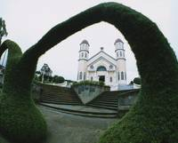 Facade of a church viewed through a topiary archw