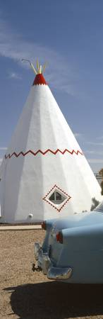 Car with a teepee in the background Wigwam Motel