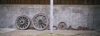 Old wagon wheels along a wall