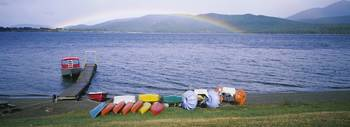 Boats on a lakeside with a rainbow in the backgro