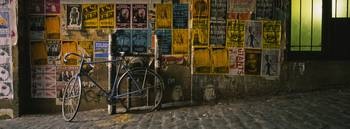Bicycle leaning against a wall with posters in an