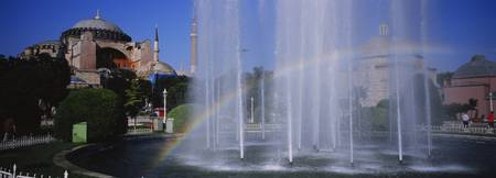 Water fountain with a rainbow in front of museum