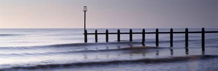 Wooden posts in an ocean Dawlish Warren Dawlish T