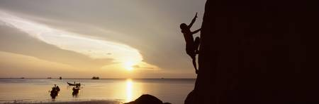 Silhouette of a person rock climbing