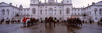 Black horse guards in front of a building
