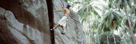 Low angle view of a man climbing up a rock face