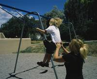 Rear view of a mother pushing her son on a swing