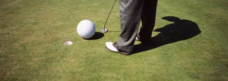 Low section view of a golfer playing golf