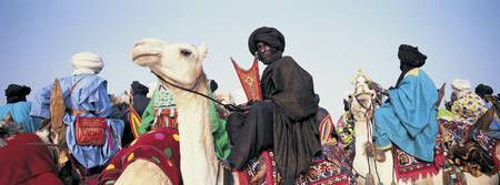Low angle view of tuaregs riding on camels