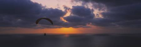 Silhouette of a person paragliding over the sea
