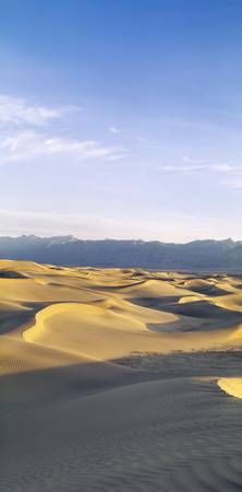 Sand dunes in a desert with a mountain range in t