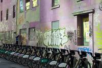 Rental Bicycles Parked beside Colorful Wall Painti