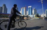 Man on Bicycle and Modern High-rises of Kunming, C