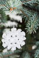 White snowflake handing on a christmas tree.