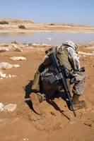 Soldier patrols along a riverbed on a search and r