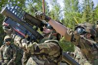 A soldier operates a missile launcher while his te