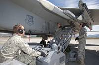 Weapons crew prepare to load an AIM-120 missile on