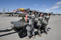 Weapons crew prepare to load an AIM-9X missile on