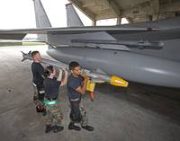 Weapons crew prepare to load an AIM-9X missile ont
