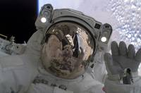 Astronaut waves at his spacewalking crewmate