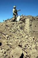 A US Army Soldier examines the rubble of a destroy