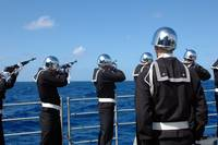 Sailors fire a gun salute during a burialatsea