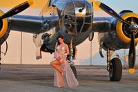 1940's pin-up girl in lingerie posing with a B-25