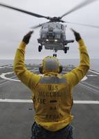 Petty Officer guides an SH-60R Sea Hawk helicopter