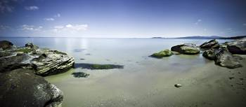 Panoramic view of tranquil sea and boulders agains