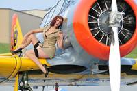 1940's style pin-up girl posing on a T-6 Texan tr