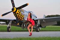1940's style pin-up girl posing with a P-51 Musta