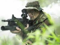 U.S. Special Forces soldier patrols through tall g