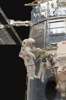 Astronauts working on the Hubble Space Telescope d