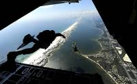 U.S. Airmen jump out of a C-130 Hercules