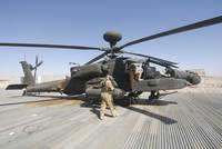 Airmen board an Apache helicopter at Camp Bastion,
