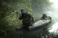 Navy SEALs navigate the waters in a folding kayak