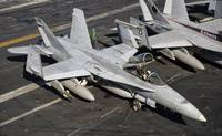 A US Navy F/A-18C Hornet parked on the flight deck