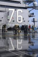 Sailors scrub the flight deck aboard the aircraft