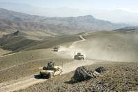 Humvees traverse rugged mountain roads