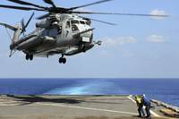 A CH-53E Super Stallion lifts off from an amphibio