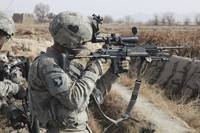 A U.S. Army soldier looks through the scope of his