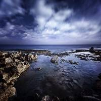 Rocky shore and tranquil sea against cloudy sky, S