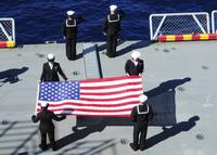 Sailors participate in a burial at sea ceremony ab