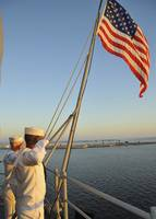 Sailors salute the national ensign aboard USS Bata