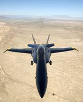A F/A18A Hornet flys over the desert landscape of