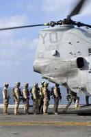 Marines board a CH-46E Sea Knight helicopter on th