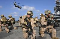 Marines position themselves on the flight deck of